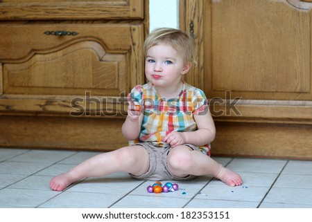 Adorable blonde toddler girl sitting indoors on tiles floor against wooden kitchen cabinetry eating delicious Easter chocolate eggs - stock photo