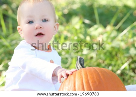 Adorable blue eyed baby boy with a pumpkin, suitable for a variety of seasonal themes - stock photo