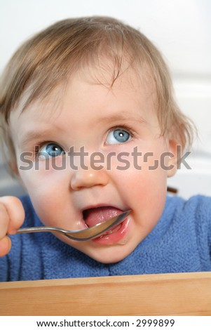 adorable blue eyed baby eating from a spoon - stock photo