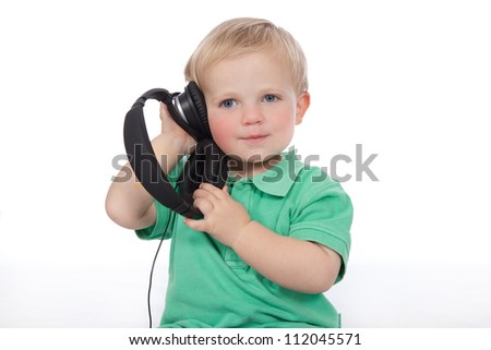 Adorable blue eyed blonde hair baby boy wearing green polo shirt and denim jeans listening to music with modern earphones - stock photo