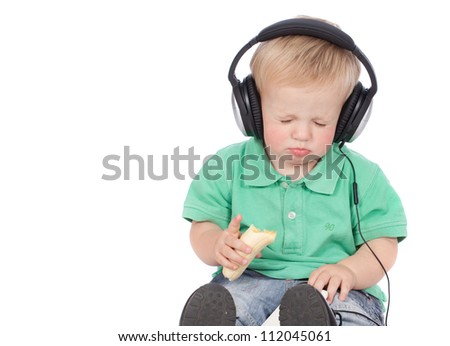 Adorable blue eyed blonde hair baby boy wearing green polo shirt listening to music with modern earphones while eating a healthy banana fruit - stock photo