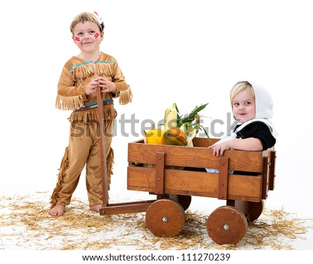 adorable boy and girl dressed as a pilgrim and indian sharing their harvest - stock photo