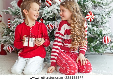 Adorable boy and girl opening presents on Christmas day - stock photo