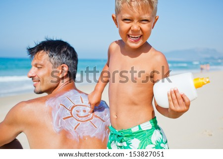 Adorable boy at tropical beach applying sunblock cream on a father's back. - stock photo