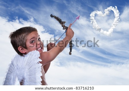 adorable boy dressed as cupid on blue sky - stock photo