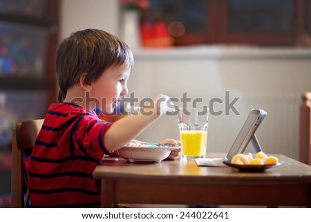Adorable boy, eating his supper, while watching movie on tablet - stock photo