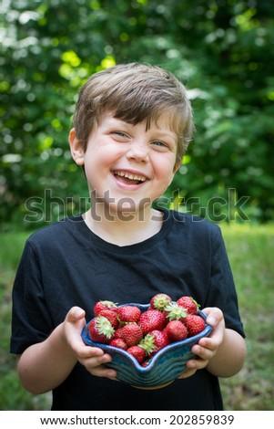 Adorable boy eats juicy, fresh strawberries - stock photo