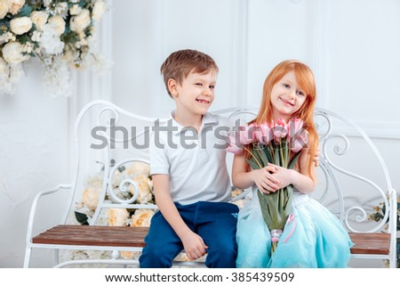 adorable boy gave the girl a bouquet of pink tulips, 8 March, birthday - stock photo