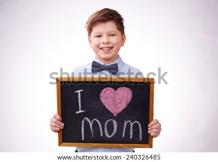 Adorable boy holding board with declaration of love to his mother - stock photo