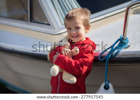 Adorable boy, holding his teddy bear, smiling at camera, standing next to a boat in a harbor