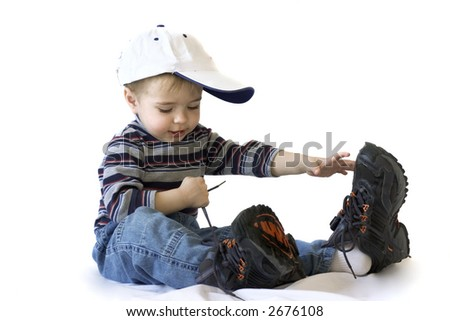 Adorable boy in big shoes tying up shoelaces