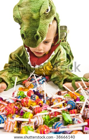 Adorable boy in crocodile Halloween costume playing trick or treat and asking for sweets. - stock photo