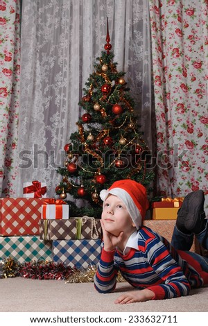 adorable boy in Santa hat dreaming about the  New Year's holidays near christmas tree - stock photo