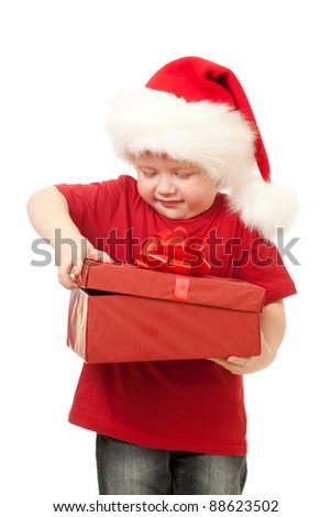 Adorable boy in Santa hat opening christmas gift in red box isolated on white - stock photo