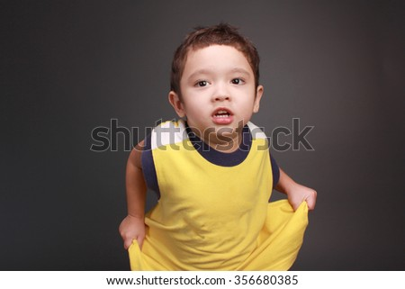 adorable boy in yellow t-shirt in studio on grey background