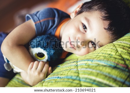 Adorable boy lying on bed, low contrast tinted photo - stock photo