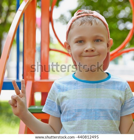 Adorable boy portrait in the summer playground - stock photo