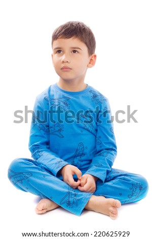Adorable boy sits cross legged on white background - stock photo