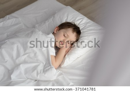 Adorable boy sleeping in bed, happy bedtime in white bedroom. Sleeping boy. Sleeping child - stock photo