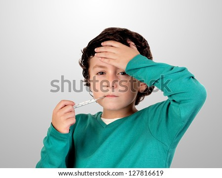 Adorable boy whit thermometer on a over grey background