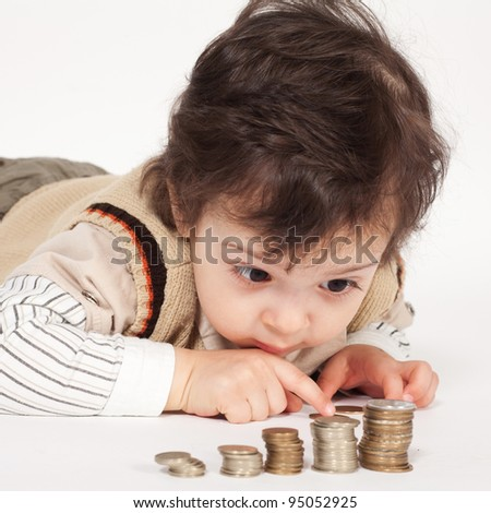 Adorable boy with a lot of coins - stock photo