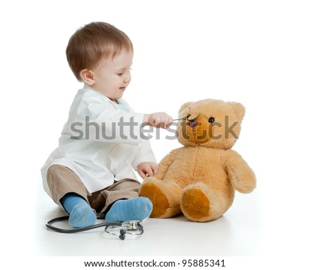 Adorable boy with clothes of doctor is spoon-feeding teddy bear over white - stock photo