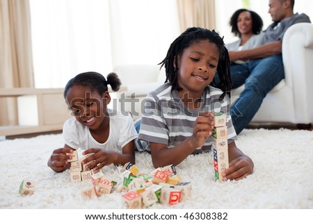 Adorable brother and sister playing alphabetic cubes lying on the floor - stock photo