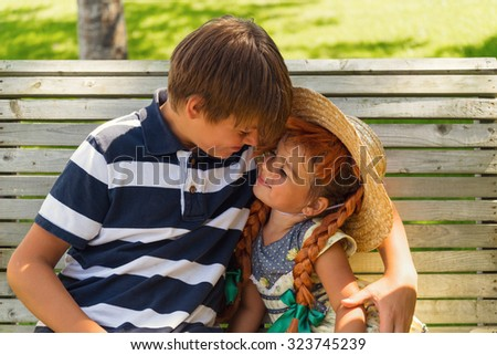 Adorable brother and sister playing together sitting on bench outdoors - stock photo