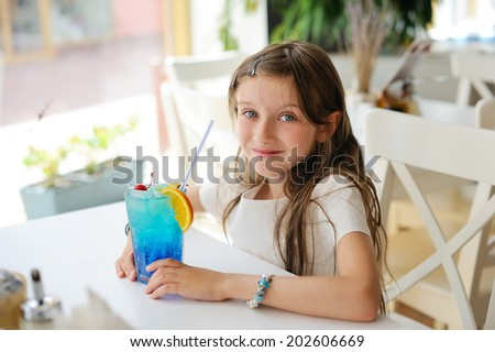 Adorable brunette kid girl sitting in the cafe with colorful juice cocktail - stock photo