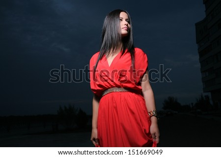Adorable brunette looking at camera with red dress posing on a dawn looking away. Fashion Beauty. Outdoors shot near river - stock photo