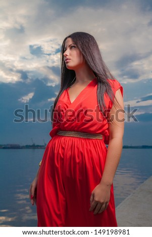 Adorable brunette with red dress posing on a dawn looking away. Fashion Beauty. Outdoors shot. - stock photo