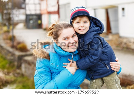Adorable caucasian little boy and mother hugging on bridge, outdoors on cold day.