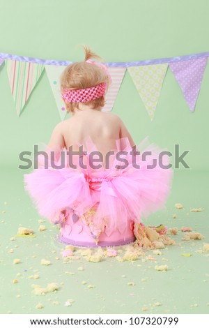 Adorable cheeky blond haired baby girl in tutu with pink head band in hair sitting on vanilla sponge cake with pink and purple hearts on icing with green seamless background and flag bunting behind - stock photo
