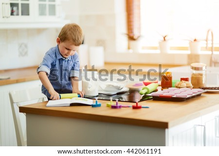 Adorable child below the age of 3  making cookies in kitchen - stock photo