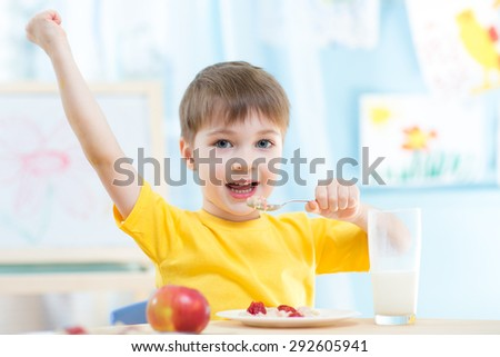 Adorable child boy eating cereal with strawberries and drinking milk - stock photo