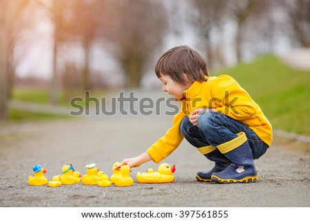 Adorable child, boy, playing in park with rubber ducks, having fun. Childhood happiness concept - stock photo
