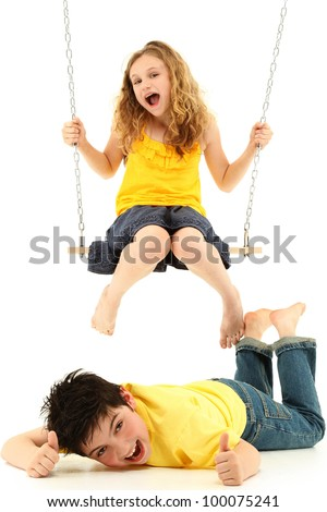 Adorable child couple portrait, girl kicks boy on ground while swinging.  Over white background. - stock photo