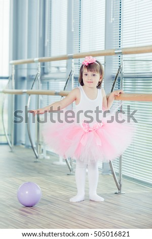 Adorable child dancing classical ballet in studio.