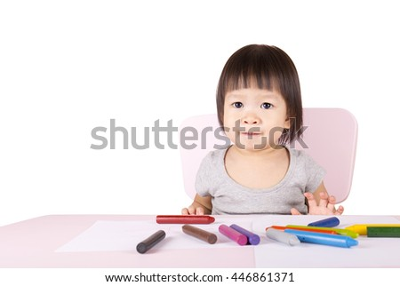 Adorable child drawing with colorful crayons and smiling, isolated on white