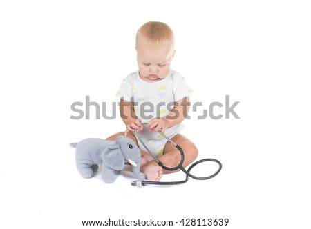 Adorable child dressed as doctor playing with toy Isolated on white background