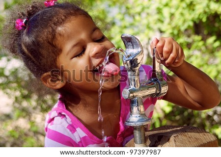 Adorable Child Drinking From Outdoor Water Fountain - stock photo