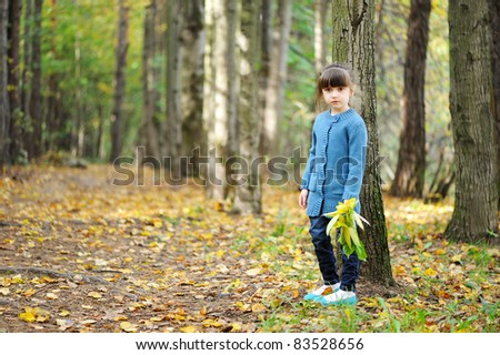 Adorable child girl in blue sweater on the road in autumn forest