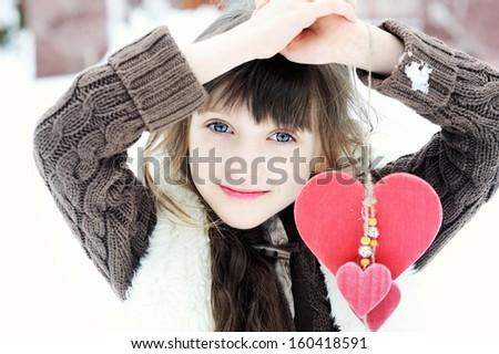 Adorable child girl in warm clothes posing outdoors, winter time - stock photo