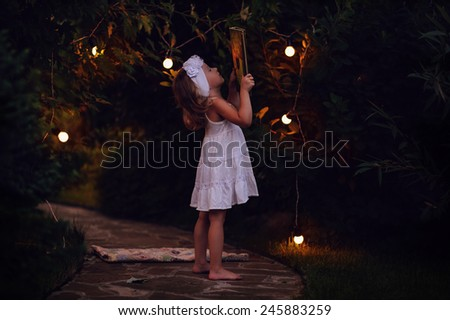 adorable child girl in white dress reading book in summer garden decorated with lights - stock photo