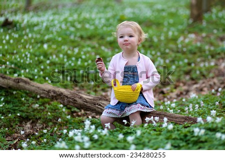 Adorable child, happy blonde toddler girl, playing in the forest full of beautiful white flowers eating chocolate and hunting for eggs on a sunny Easter day - stock photo