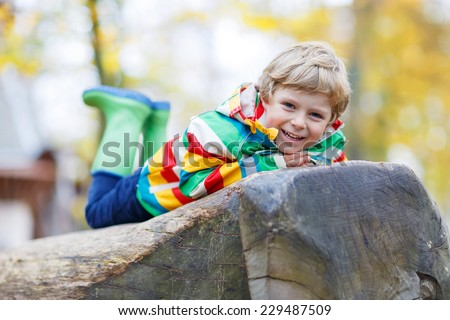Adorable child in colorful rain jacket with stripes and gumboots having fun with playing on playground on warm, autumn day, outdoors - stock photo
