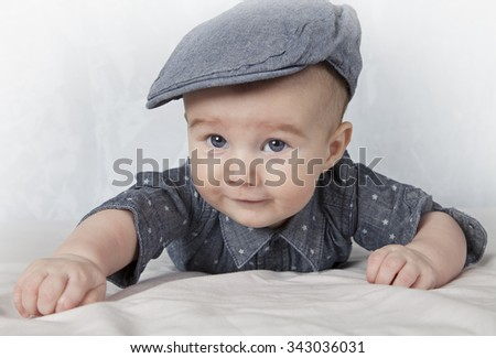 Adorable child in the cap lying on his tummy  - stock photo