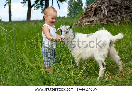 adorable child is cuddling a baby goat