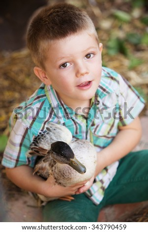 Adorable child playing with little duck outdoors