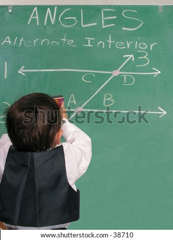 Adorable child prodigy at the chalkboard doing math equations. - stock photo